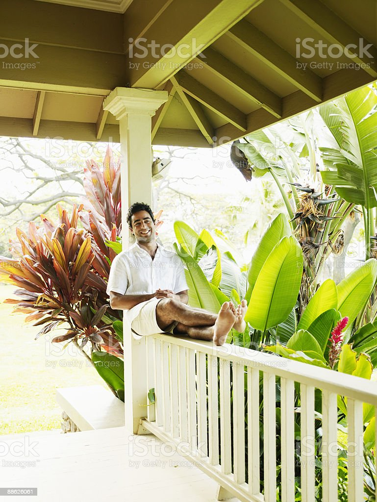 Man sitting on railing of tropical home smiling royalty-free stock photo