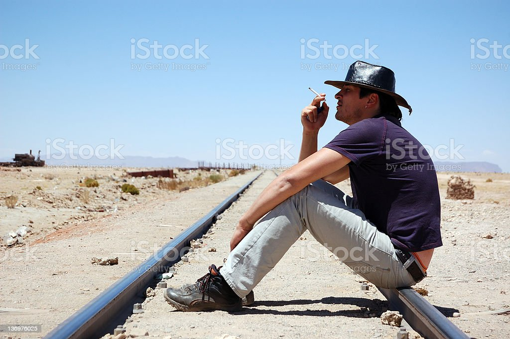 Man sitting on railway and smoking royalty-free stock photo