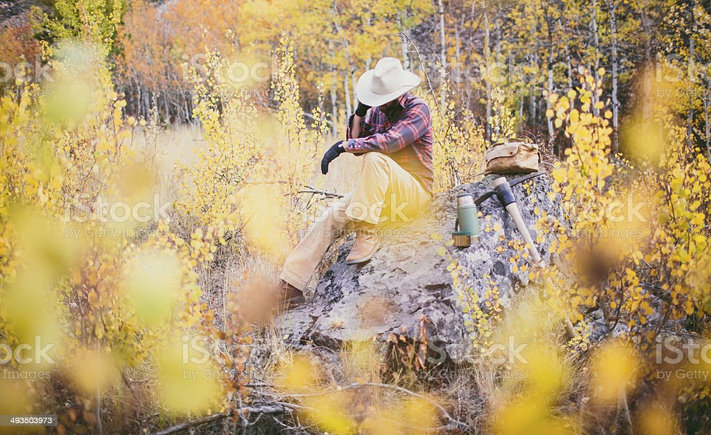 Man sitting on rock in the woods of Montana stock photo