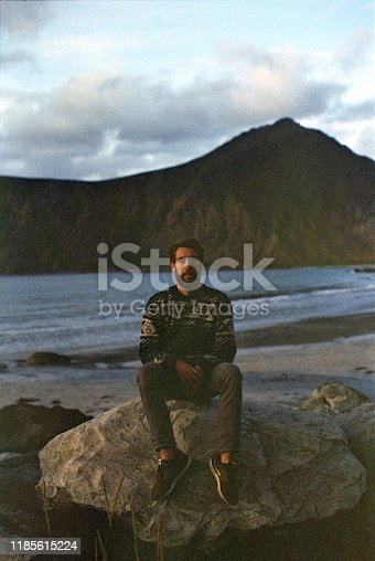 Young Caucasian man sitting on rock on beach on Lofoten island