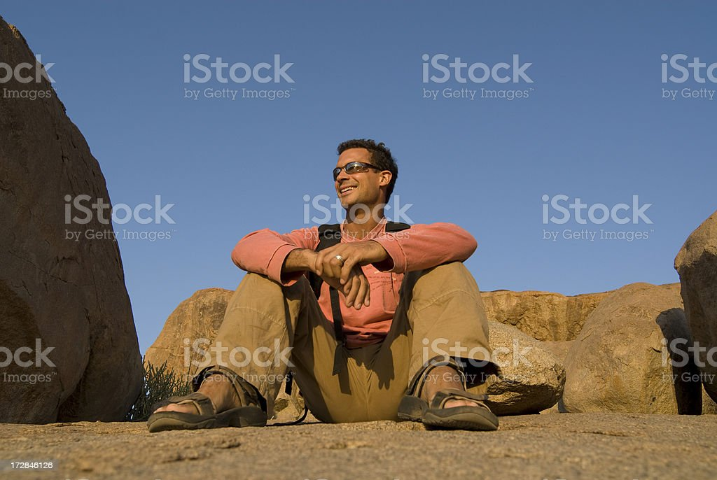 Man sitting on rocks stock photo