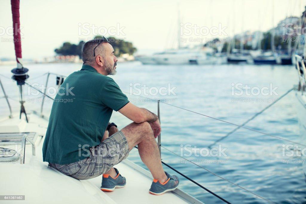 Man sitting on sailboat's bow and enjoying stock photo