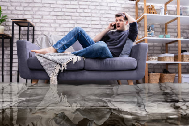 man sitting on sofa calling to plumber - flooded room stock photos and pictures