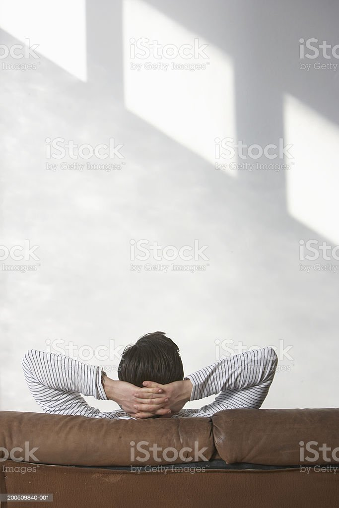 Man sitting on sofa, hands behind head, rear view stock photo