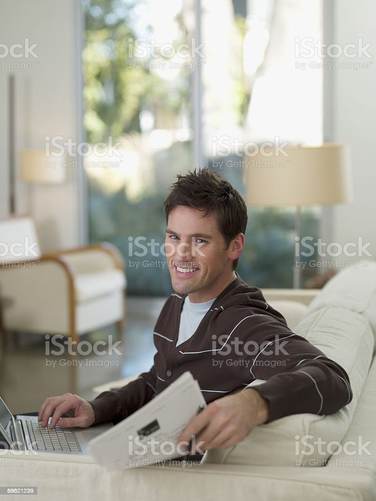 Man sitting on sofa holding papers royalty-free stock photo
