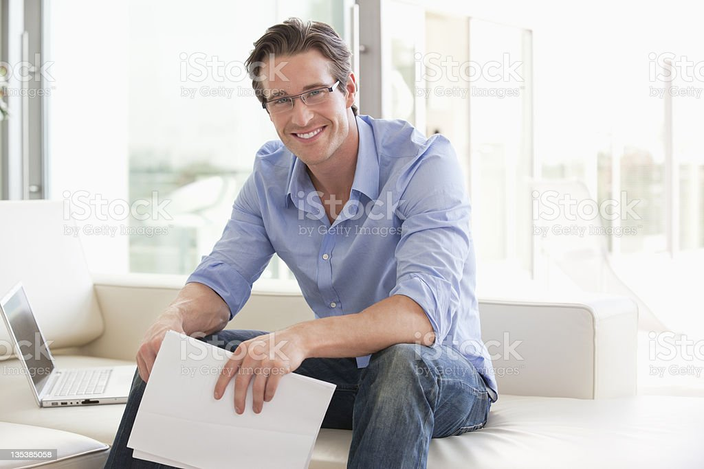 Man sitting on sofa holding paperwork royalty-free stock photo