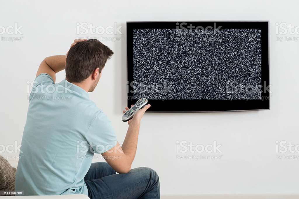 Man Sitting On Sofa In Front Of Television stock photo