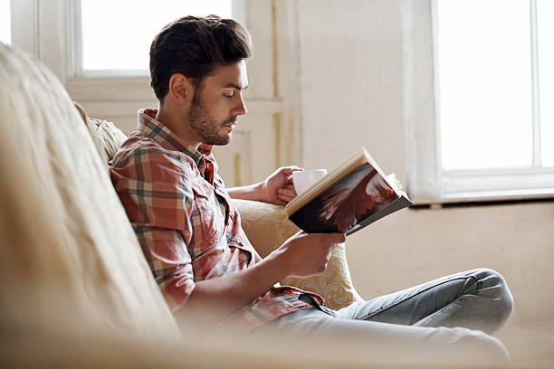 man sitting on sofa reading book - london themenzimmer stock-fotos und bilder