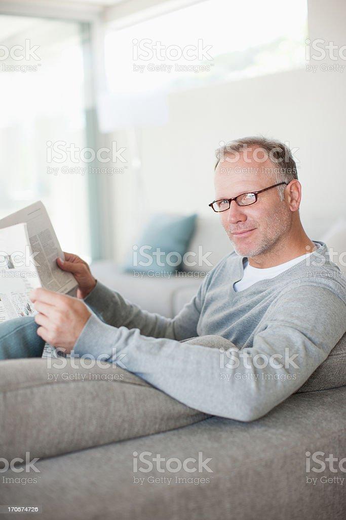 Man sitting on sofa reading newspaper royalty-free stock photo