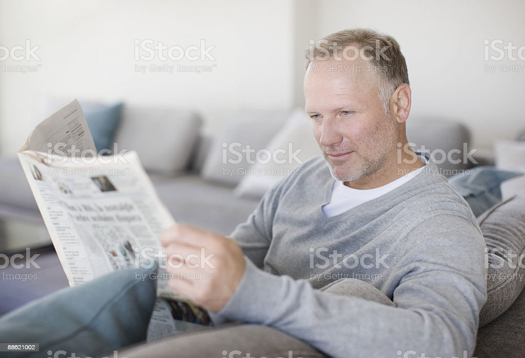 Man sitting on sofa reading newspaper royalty-free stock photo