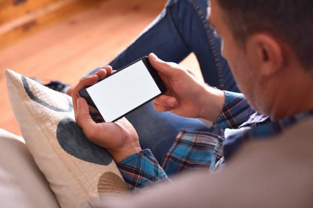坐在沙發上觀看智慧手機多媒體內容的男子 - 橫向 個照片及圖片檔