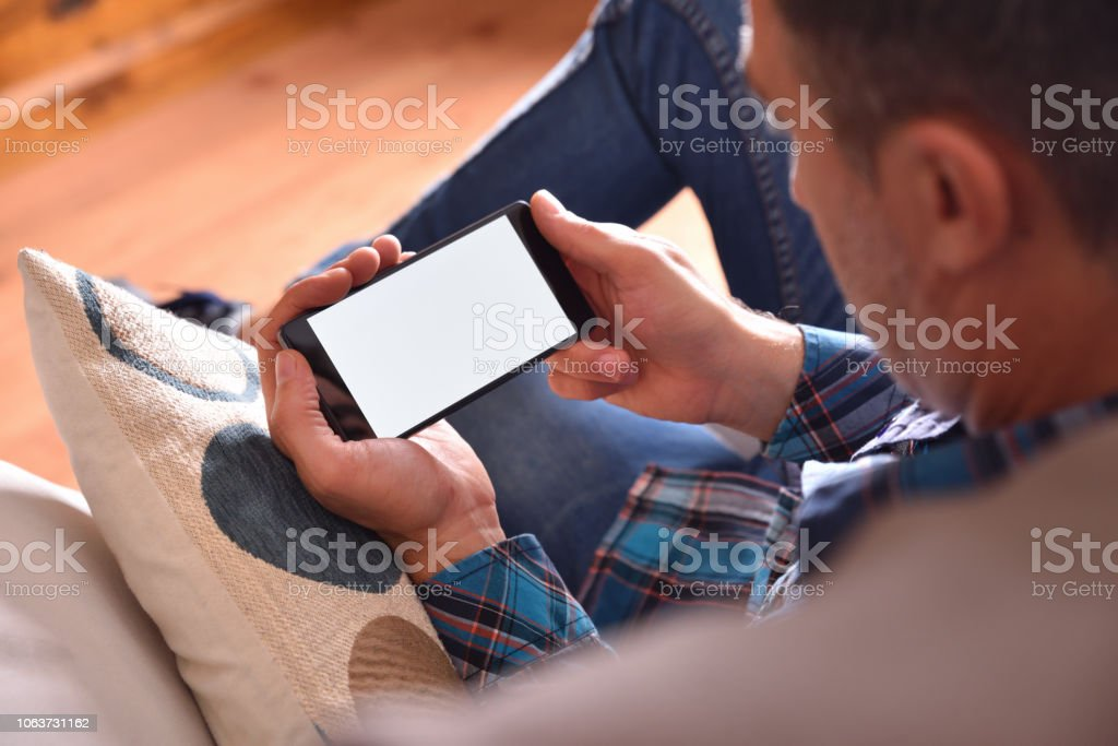 Man sitting on sofa watching multimedia content on a smartphone stock photo