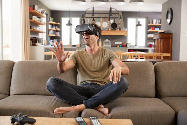 mann sitzt auf dem sofa tragen virtual-reality-kopfhörer - einzelner mann über 30 stock-fotos und bilder