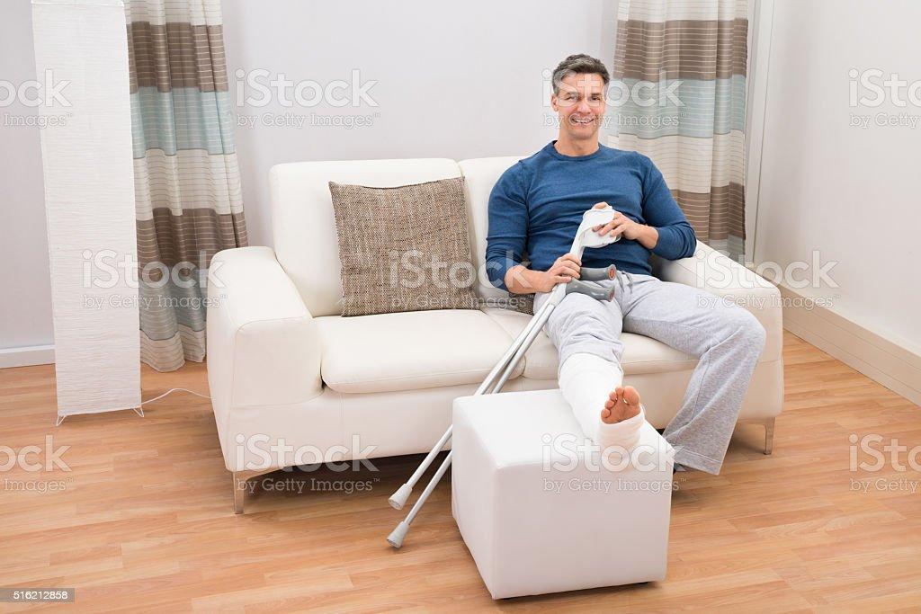 Man Sitting On Sofa With Crutches stock photo