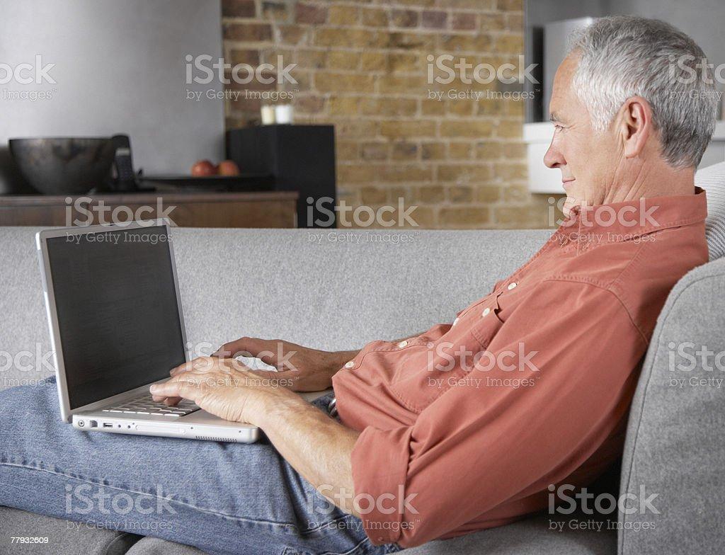 Man sitting on sofa with laptop stock photo