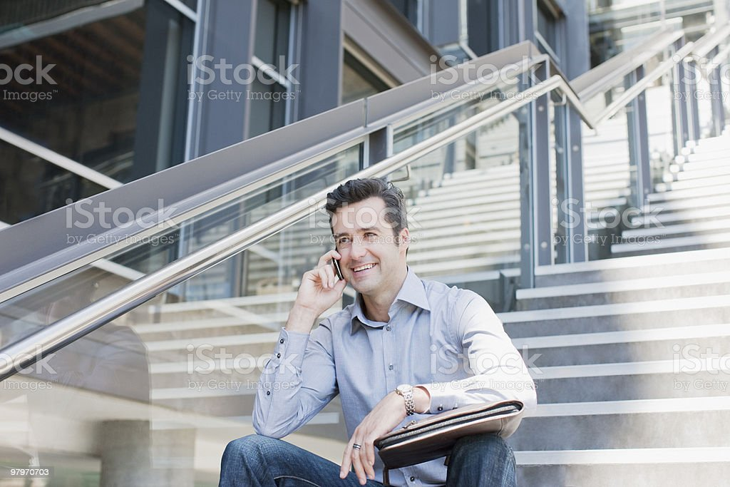 Man sitting on stairs and talking on cell phone royalty-free stock photo