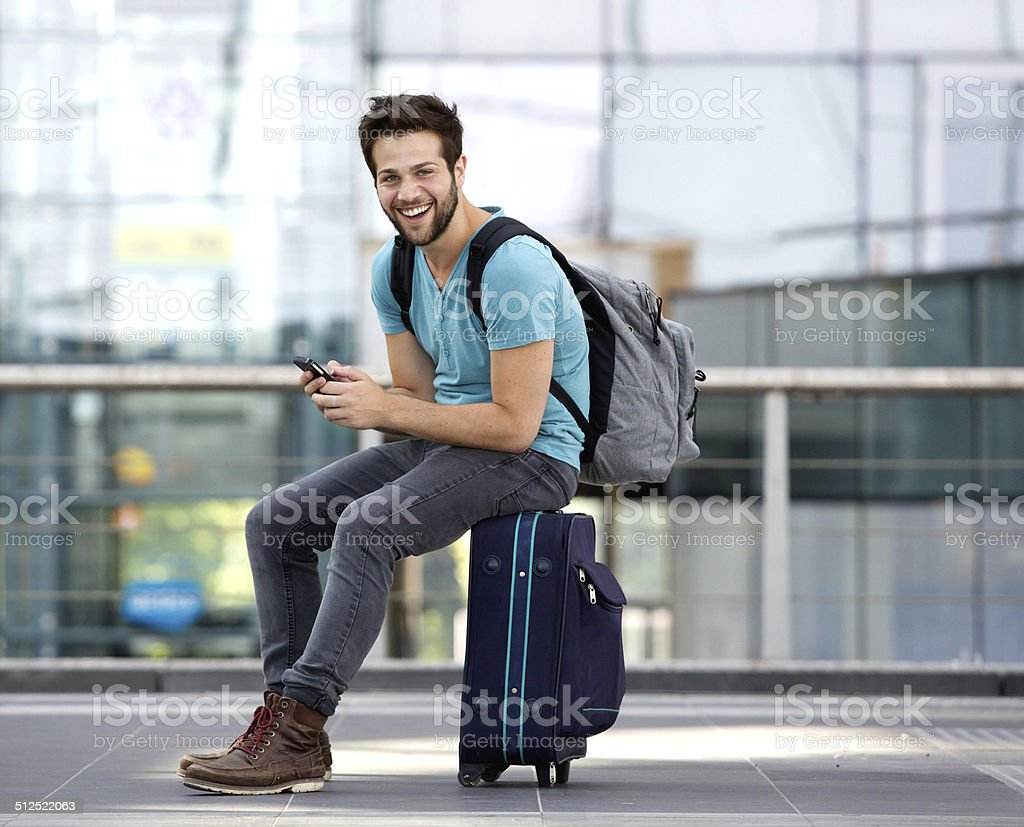 Man sitting on suitcase and sending text message stock photo