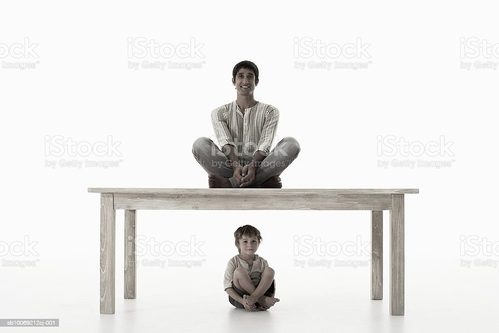 Man sitting on table, boy (4-5 years) sitting below, against white background, portrait royalty-free stock photo