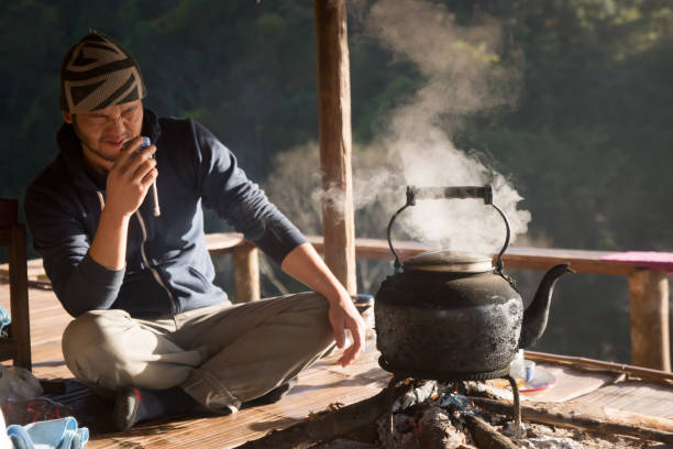 CHIANGMAI, THAILAND, JAN 30, 2018: Man sitting on the bamboo floor and testing tea from vintage iron kettle in organic tea field at Doi Angkang. Doi Angkang is the high land at the north of Thailad stock photo