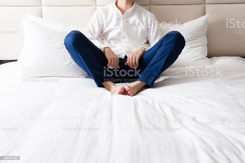 Man sitting on the bed royaltyfri bildbanksbilder