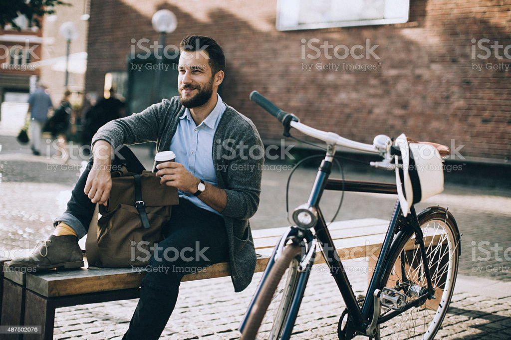Man sitting on the bench and enjoying coffee stock photo