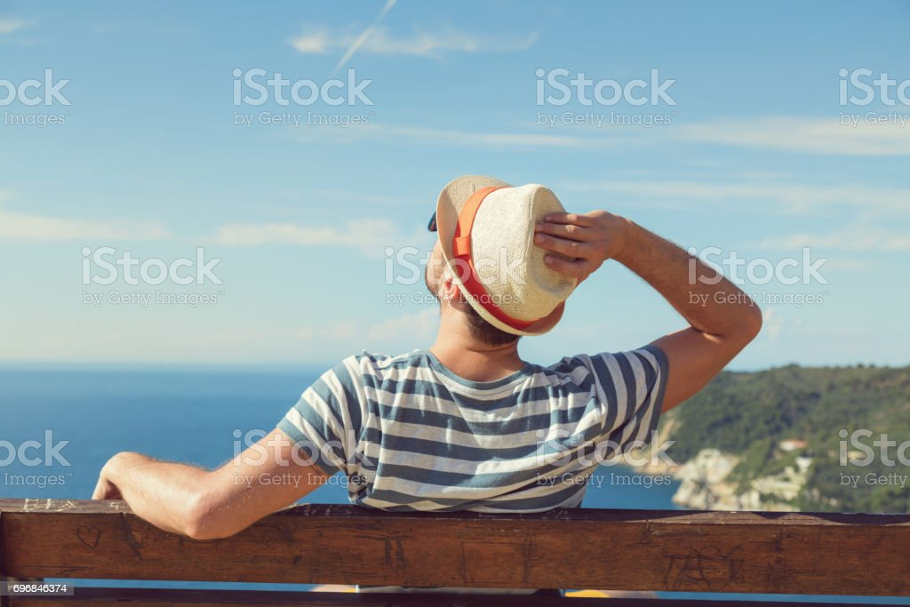 Man sitting on the bench and enjoying the view. stock photo