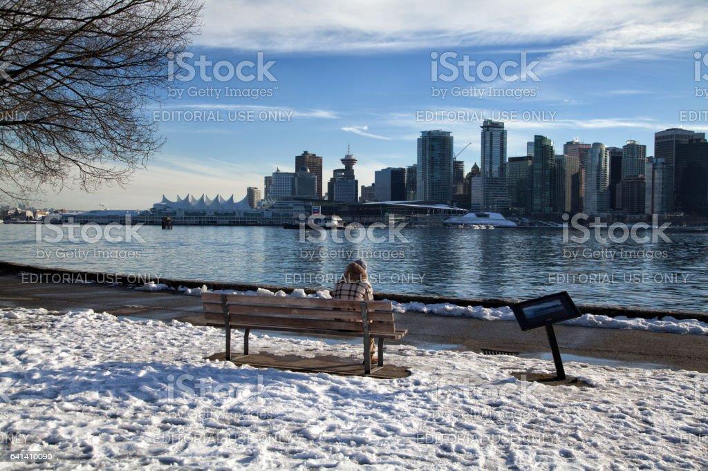 Man sitting on the bench enjoying the Vancouver skyline stock photo