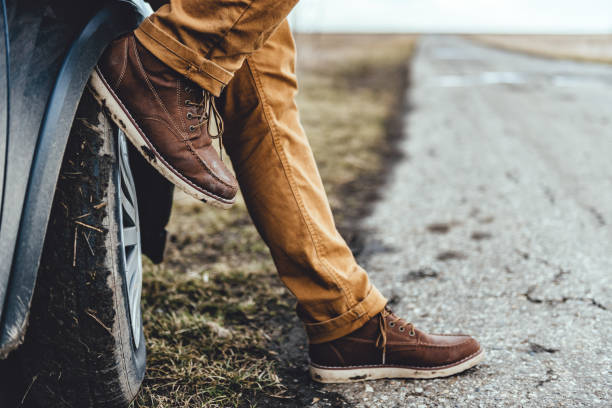 man sitting on the car - dirty shoes stock photos and pictures