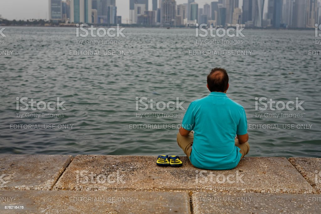 Man sitting on the Doha cor niche and looking to Arabic gulf stock photo