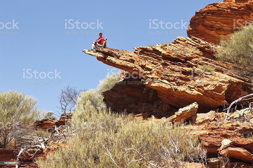 Man sitting on the edge of a huge rock in the distance stock photo