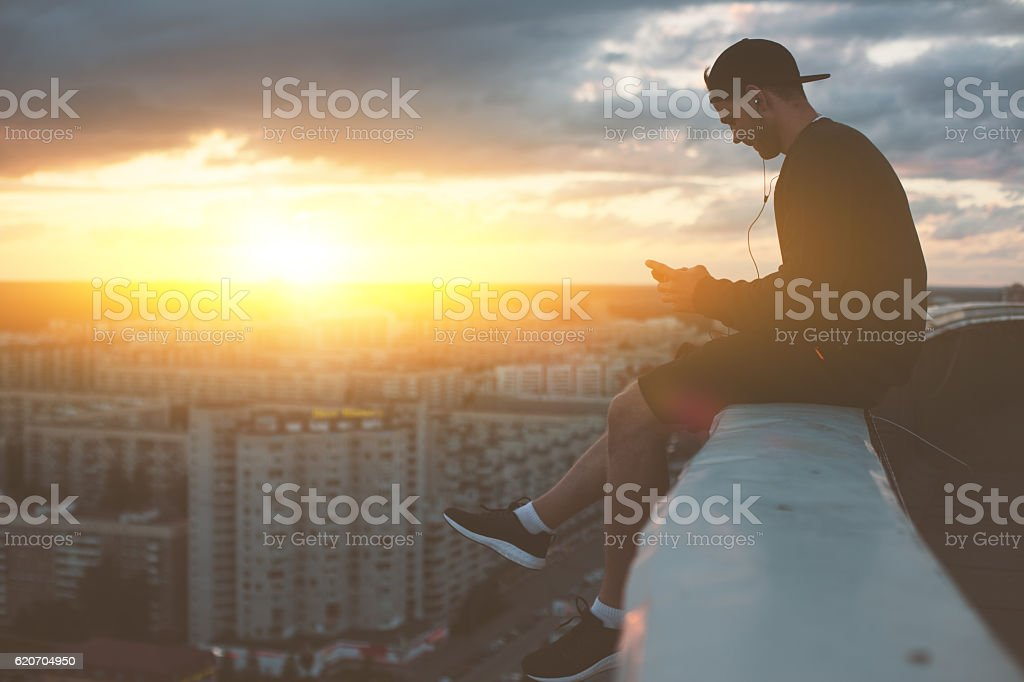 Man sitting on the edge of the roof with smartphone stock photo