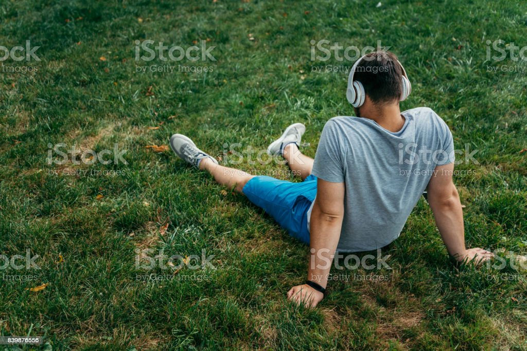 man sitting on the ground in city park stock photo