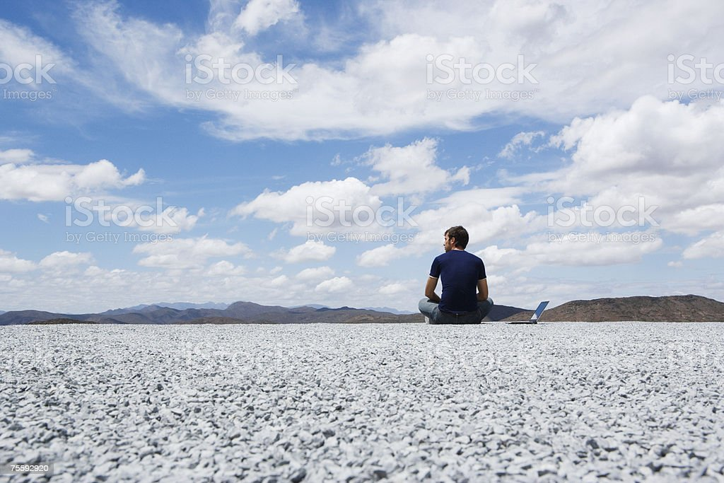 Homem sentado no chão com seu computador portátil foto de stock royalty-free