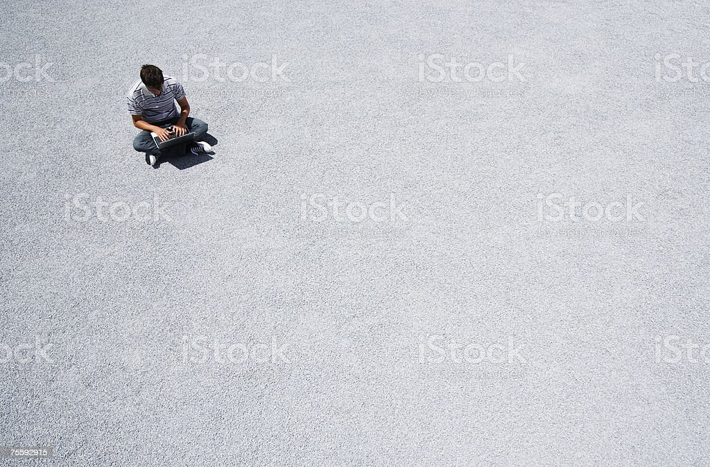 Man sitting on the ground working on his laptop computer royalty-free stock photo