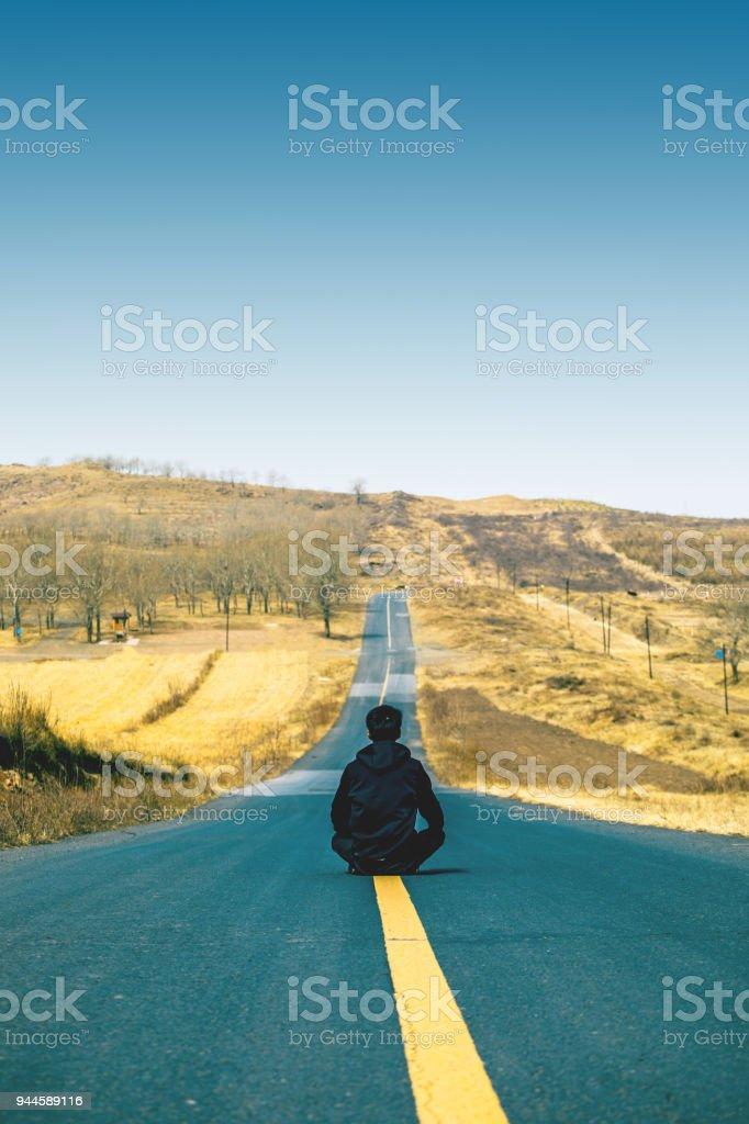 Hombre Sentado En El Medio Del Camino Foto De Stock Y Más Banco De Imágenes De Adulto Istock