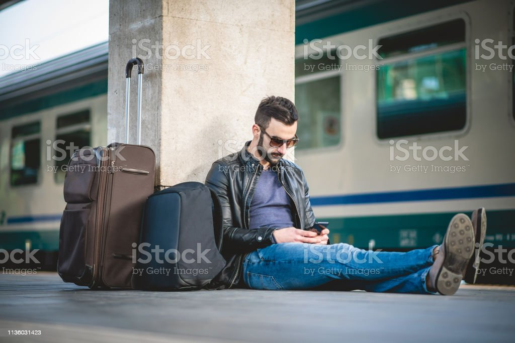 Man Sitting on the Railroad Station Platform and waiting for a train