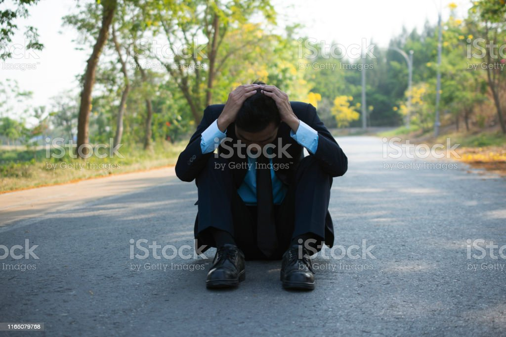 Man sitting on the road because of disappointment. The business failed