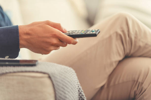 Mann sitzt auf dem Sofa und schaut Fernsehen. Er hält eine TV-Fernbedienung. – Foto