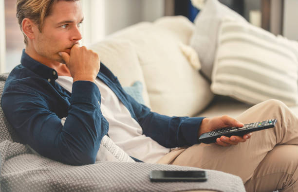 Man sitting on the sofa watching television. Man sitting on the sofa watching television. He is holding a tv remote control. He looks serious and like he is thnking changing channels stock pictures, royalty-free photos & images