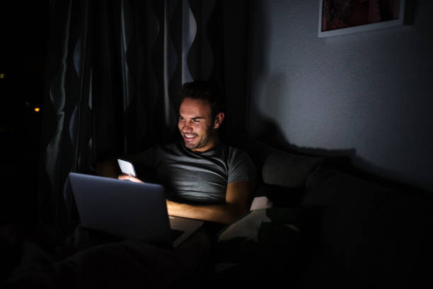 Man sitting on the sofa with a mobile phone and computer stock photo