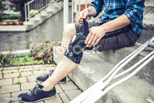 man sitting on the steps and adjusting his orthosis after having knee sprain accident while playing soccer