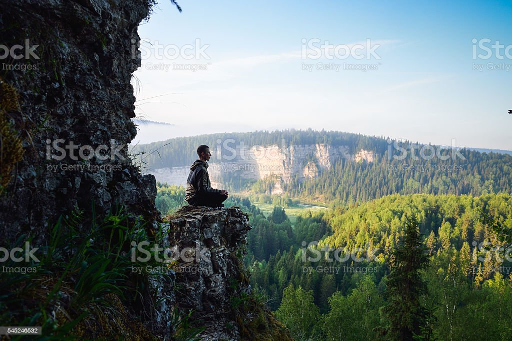 Man sitting on the top of the mountain in yoga - foto de stock