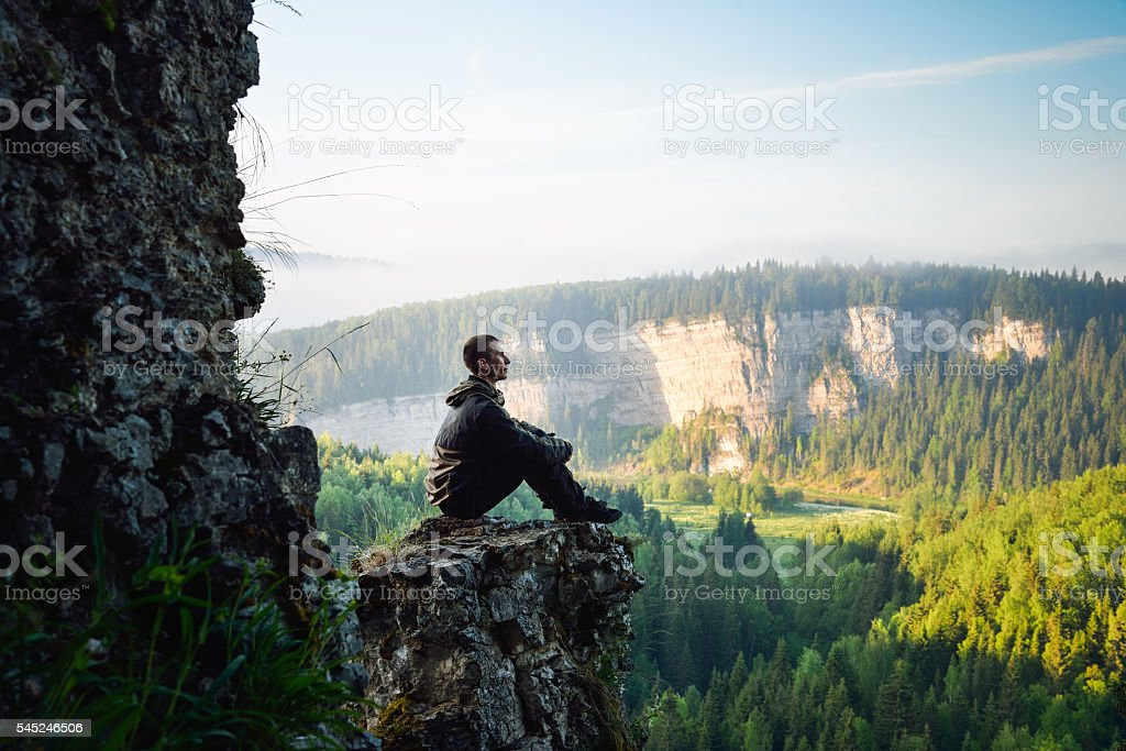 Man sitting on the top of the mountain, leisure in stock photo
