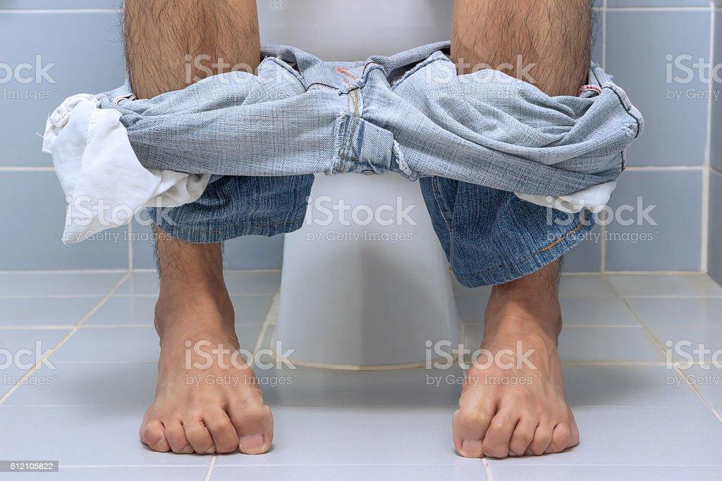 Man sitting on toilet, diarrhea stock photo