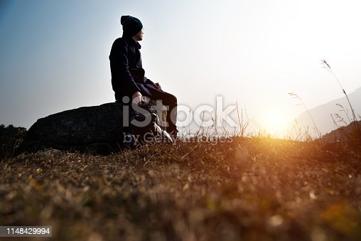 A man sitting on top of mountain.