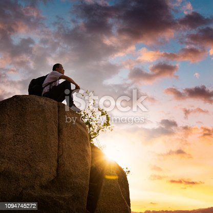 Man sitting on top of the mountain.