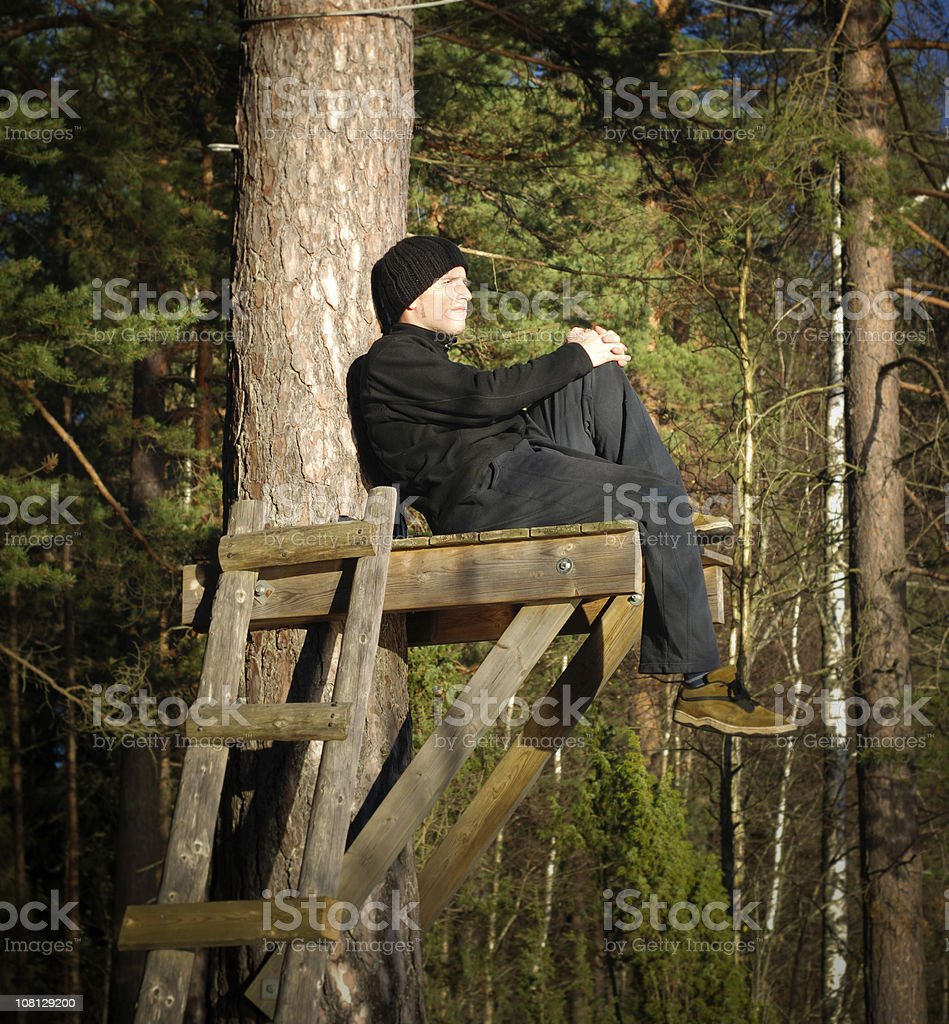Man Sitting on Tree Observation Point royalty-free stock photo