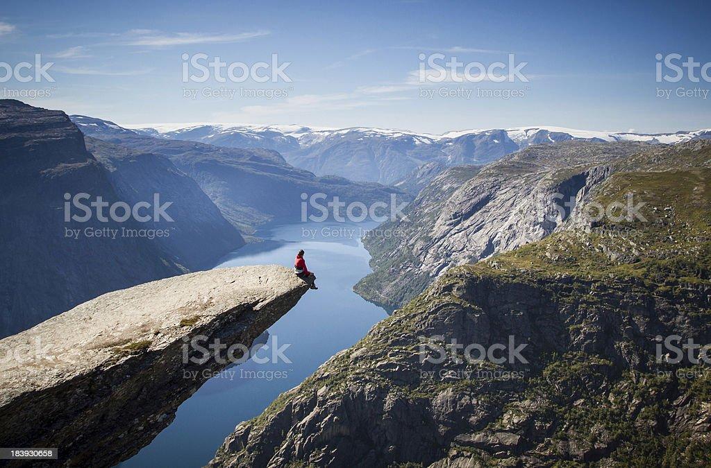Człowiek siedzi na trolltunga w Norwegii - Zbiór zdjęć royalty-free (Aranżować)