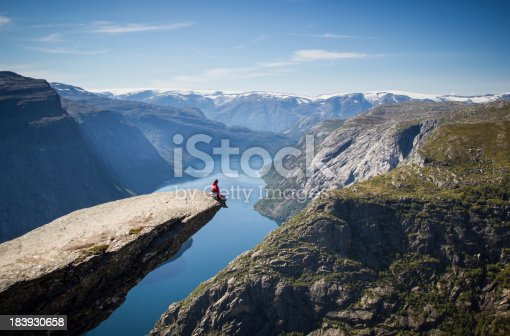 man sitting on trolltunga rock above a norwegian fjord.