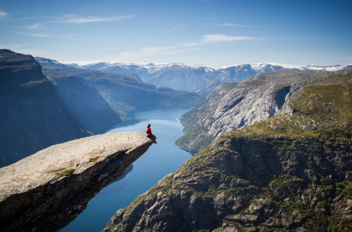 man sitting on trolltunga rock above a norwegian fjord.